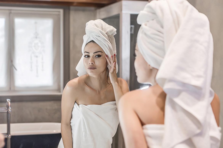 девушка смотрит в зеркало после процедуры