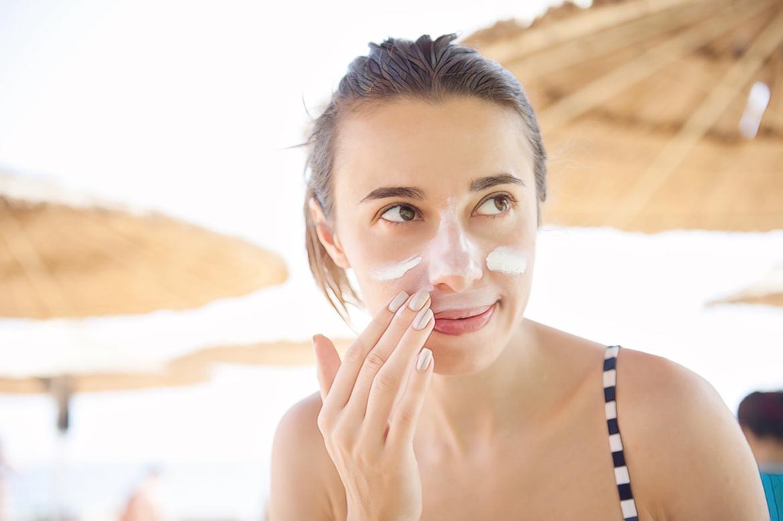 девушка мажет лицо солнцезащитным кремом