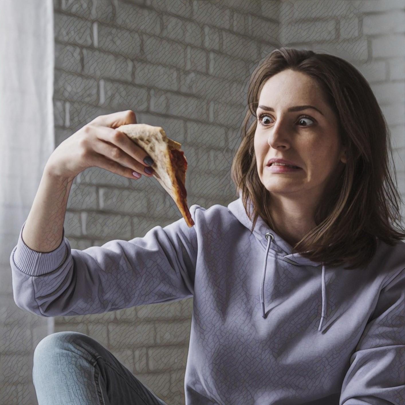 Женщина ест пиццу дома