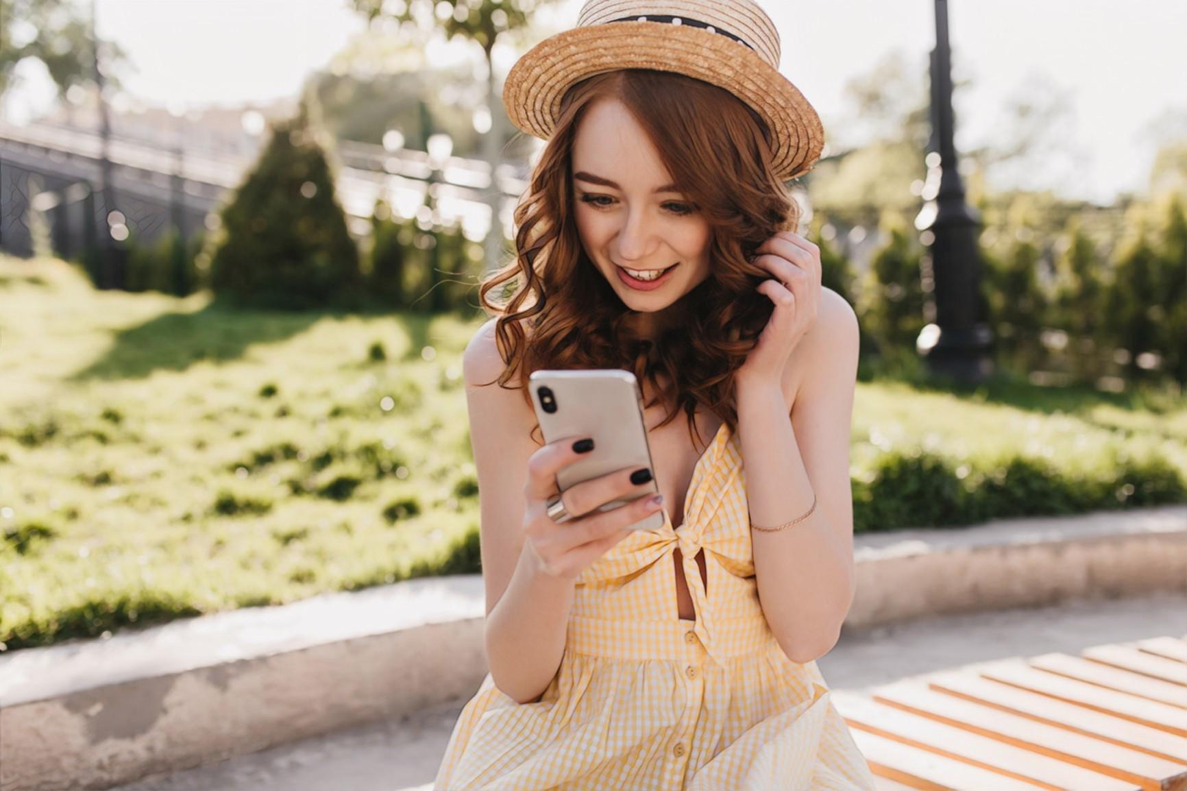 девушка читает о своей коже  с телефона