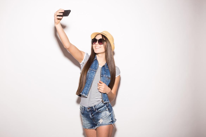 Девушка фотографирует себя, чтобы прхвастаться своей чистой кожей