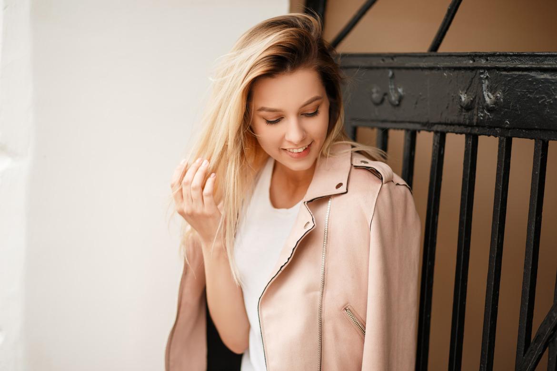 женщина в модной розовой куртке на природе