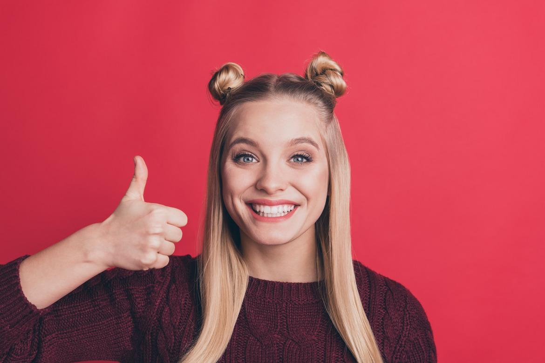 Милая девушка улыбается и показывает большой палец