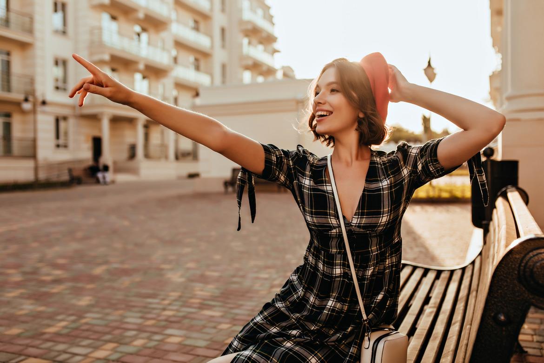 Очень радостаная девушка сидит на лавочке и держит шляпу, чтобы она не улетела