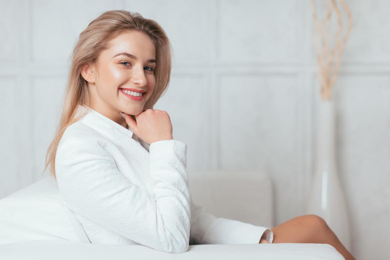 Девушка с красивой кожей улыбается на кресле