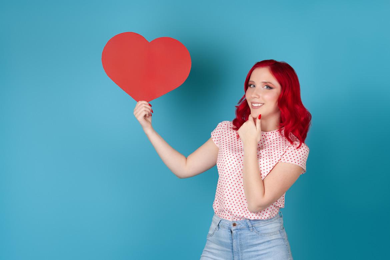 Девушка улыбается, держа бумажное сердце