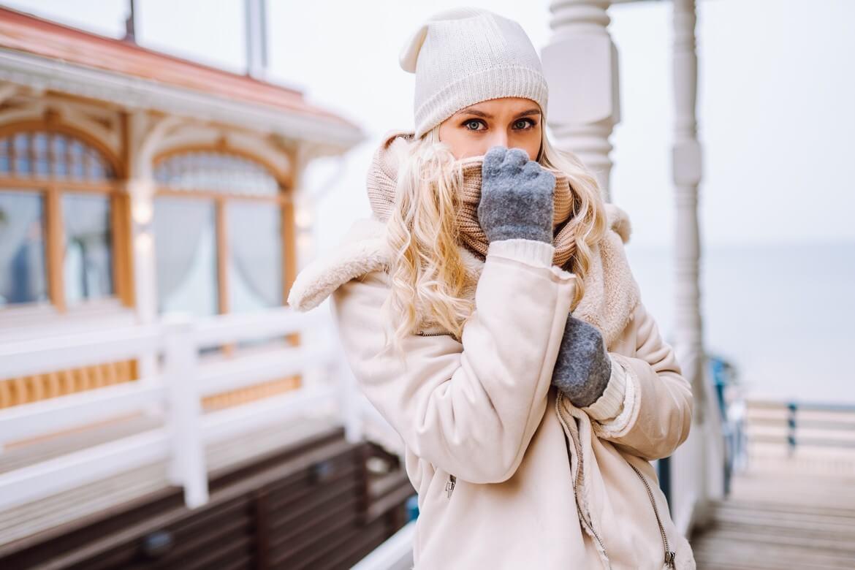 Милая девушка прячет лицо шарфом