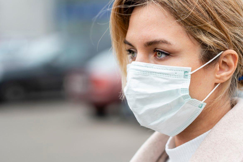 Красивая женщина гуляет по улице в маске