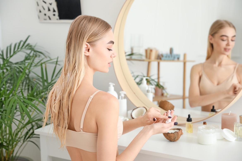 Девушка в ванной импользует средство для лица