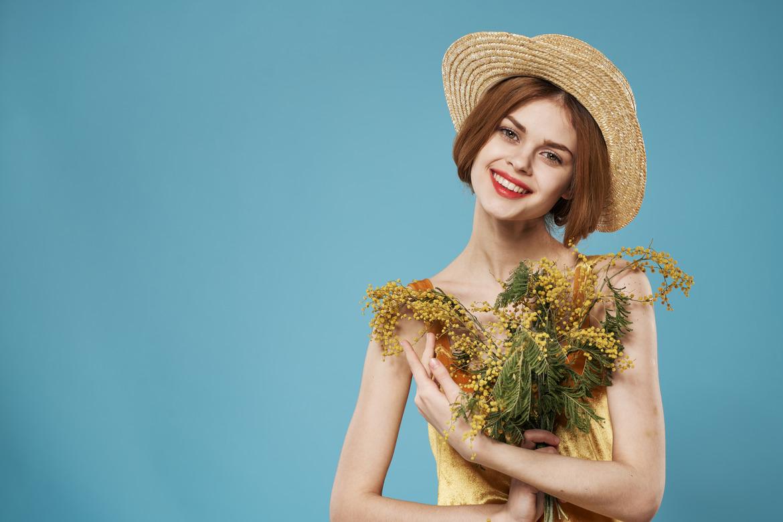Девушка в шляпе с цветами улыбается