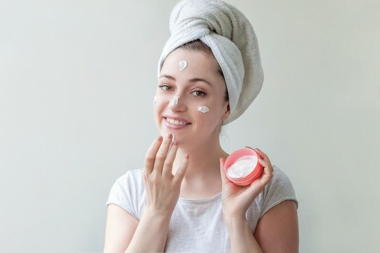 Портрет красоты женщины в полотенце на голове с белой питательной маской