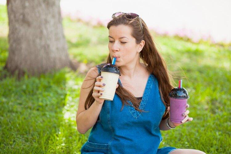 Молодая женщина пьет банановый смузи в парке