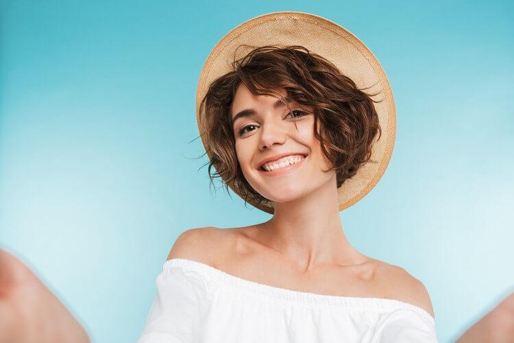 Портрет улыбающейся молодой женщины, делающей селфи