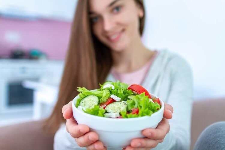Здоровая веганская женщина, держащая миску салата из свежих овощей