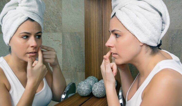 Крупным планом молодая женщина с полотенцем над волосами сжимает прыщ на ее красивом лице перед зеркалом