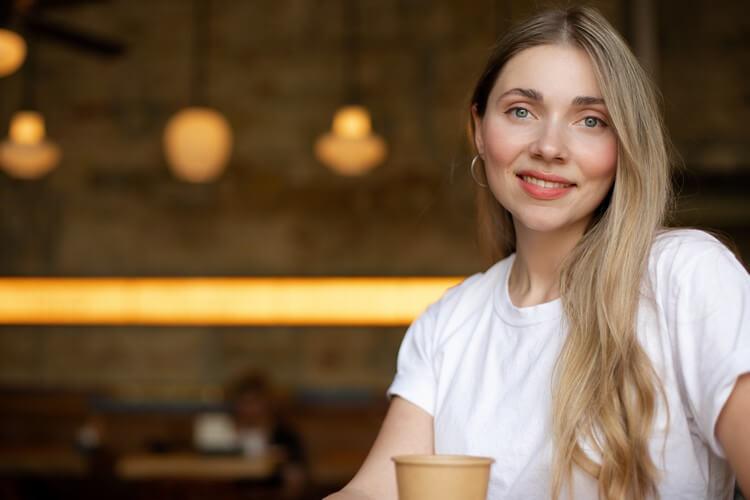 Крупный план улыбающейся блондинки в белой футболке, которая сидит в кафе