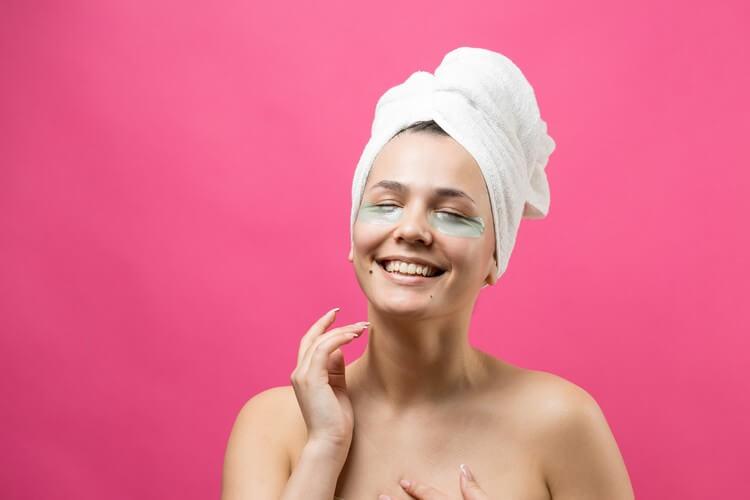 Молодая красивая девушка в белом полотенце на голове носит пластыри из коллагенового геля под глазами.маска под глаза уход за лицом.