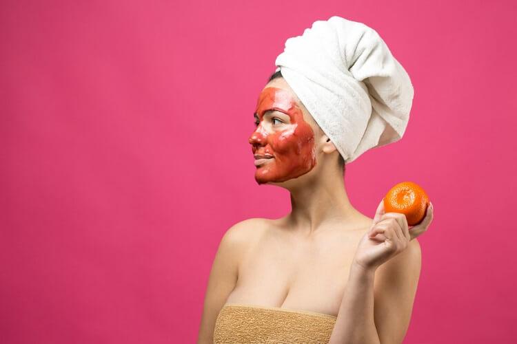 Портрет красоты женщины в белом полотенце на голове с красной питательной маской