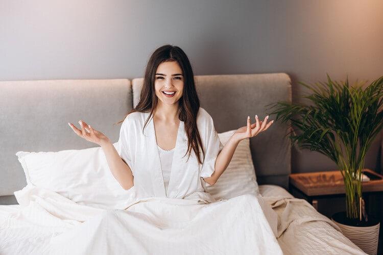 Молодая женщина с удивленным лицом сидит в постели