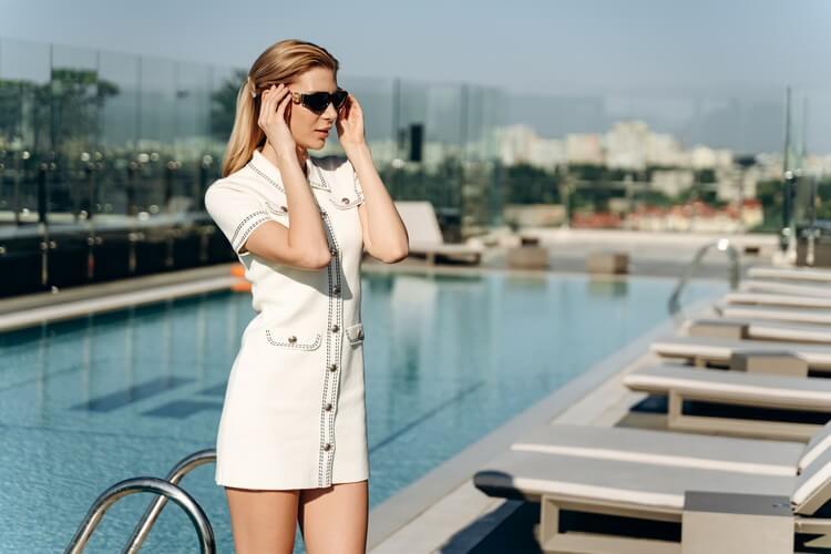 Привлекательная блондинка в стильной одежде поправляет солнцезащитные очки