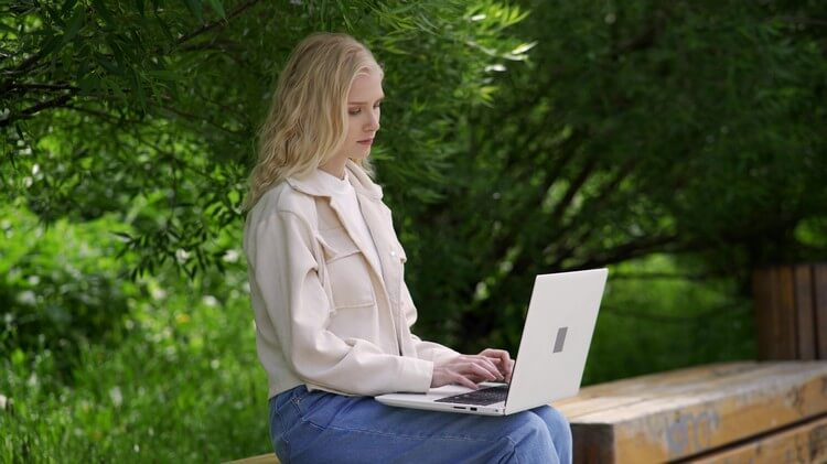 Молодая студентка сидит на скамейке в парке с ноутбуком.