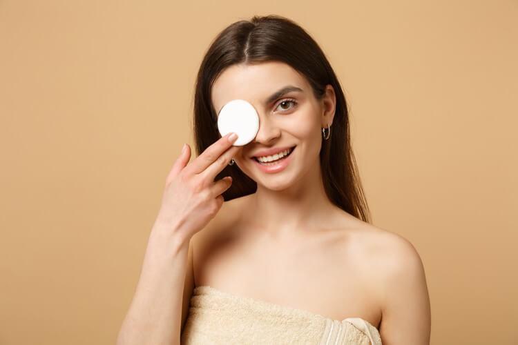 Девушка прикрывает глаз ватным диском