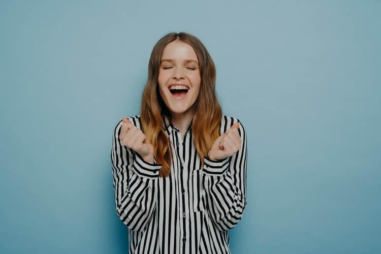 Смеющаяся девочка-подросток, одетая в рубашку со сжатыми кулаками, кричащая от счастья