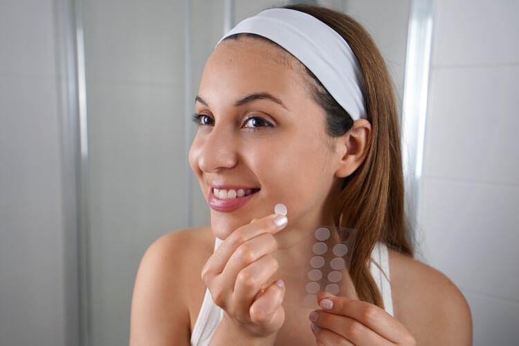 Красивая улыбающаяся девушка накладывает пластырь для лечения прыщей на прыщ в ванной комнате